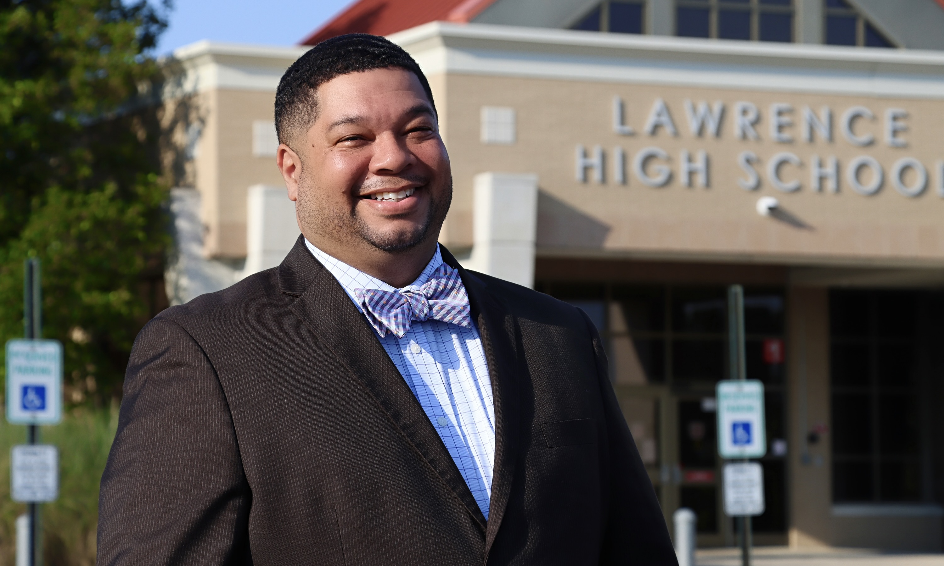 Portrait of Clifton Thompson in front of Lawrence High School (Eshaya Draper/Office of the Superintendent)