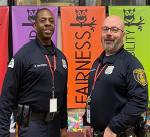 An African American man & Caucasian man in police uniforms standing in front of colorful banners