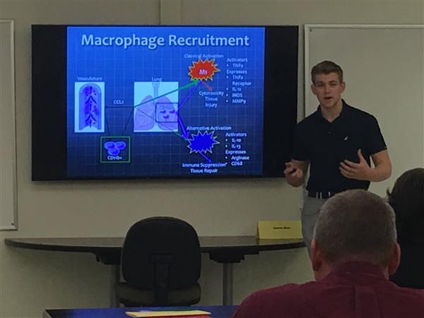 Teen boy in front of screen of PPT slide entitled Macrophage Recruitment