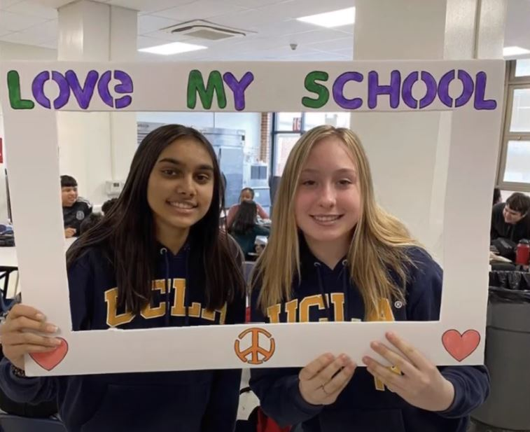 2 girls looking through paper frame with text Love My School