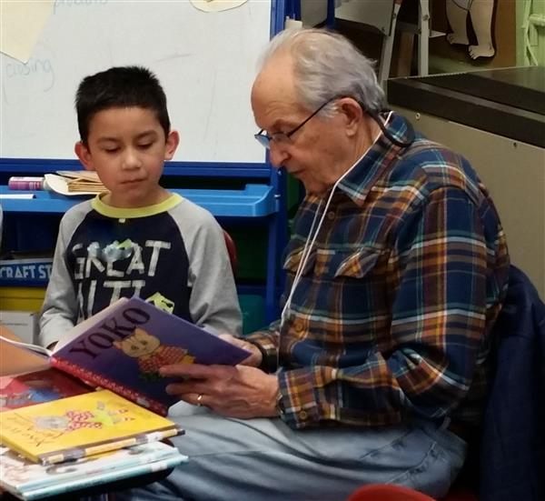 GrandPal reading to boy at Slackwood School