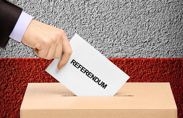 Hand putting referendum vote into voting box